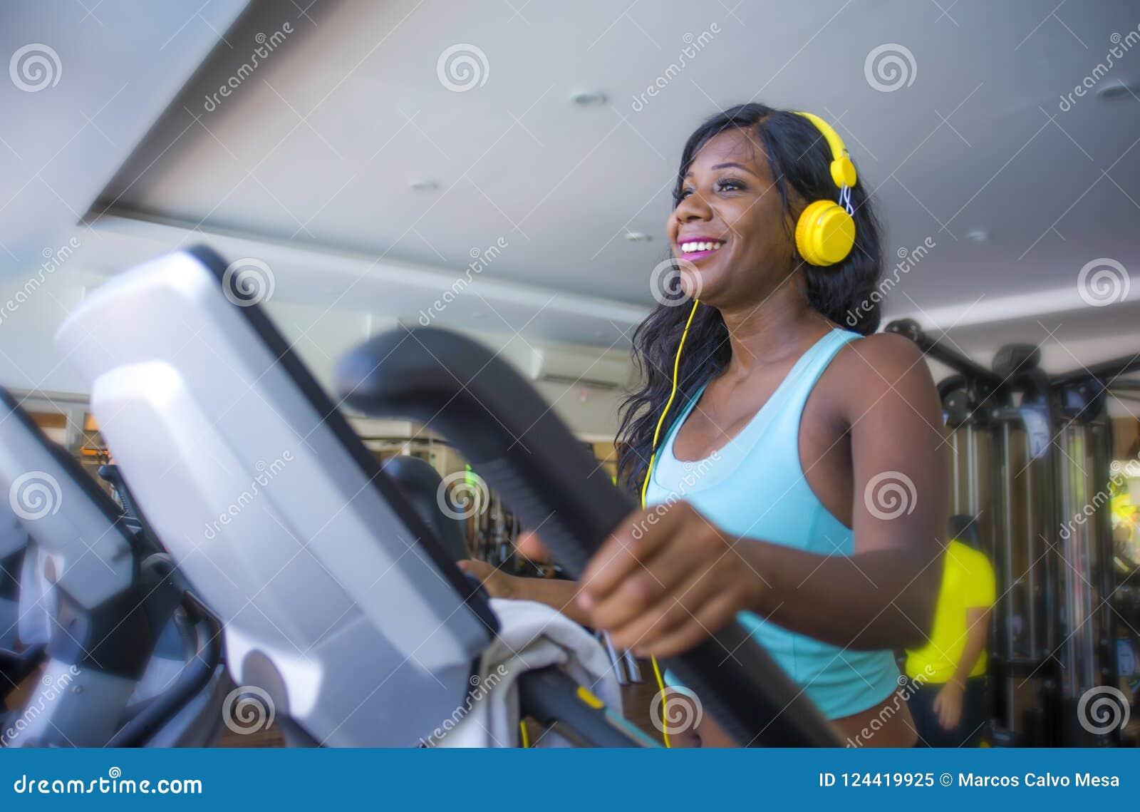 Binnen gymnastiekportret van jonge aantrekkelijke en gelukkige zwarte Afrikaanse Amerikaanse vrouw die met hoofdtelefoons ellipti