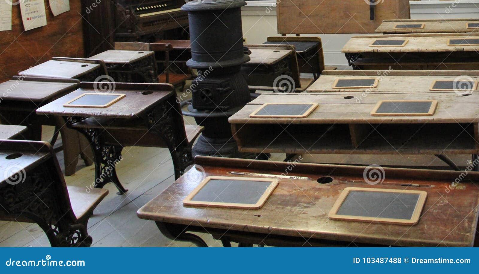 Binnen het oude uitstekende houten klaslokaal met brandplaats in het midden
