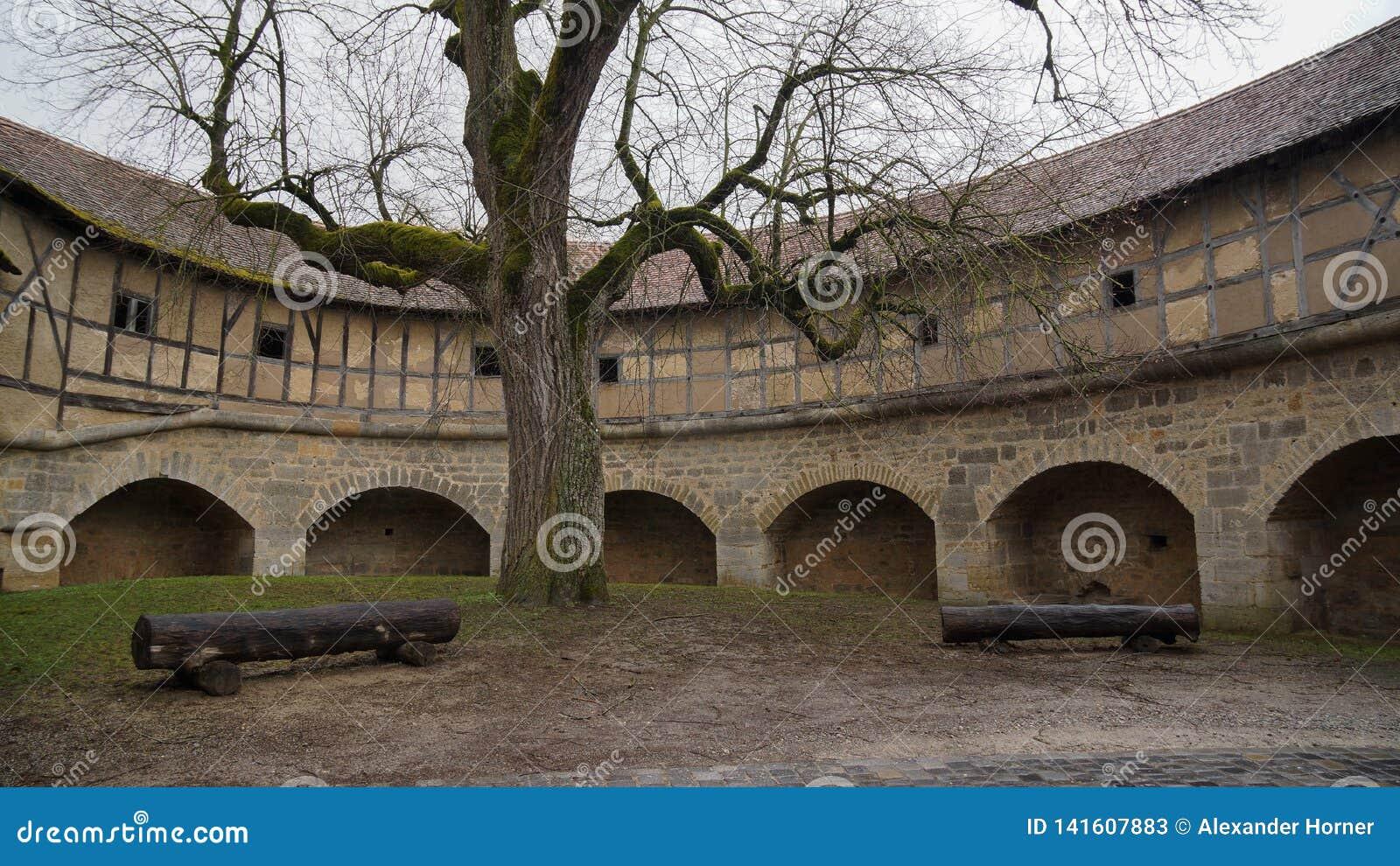 Binnenbinnenplaats met boom en banken