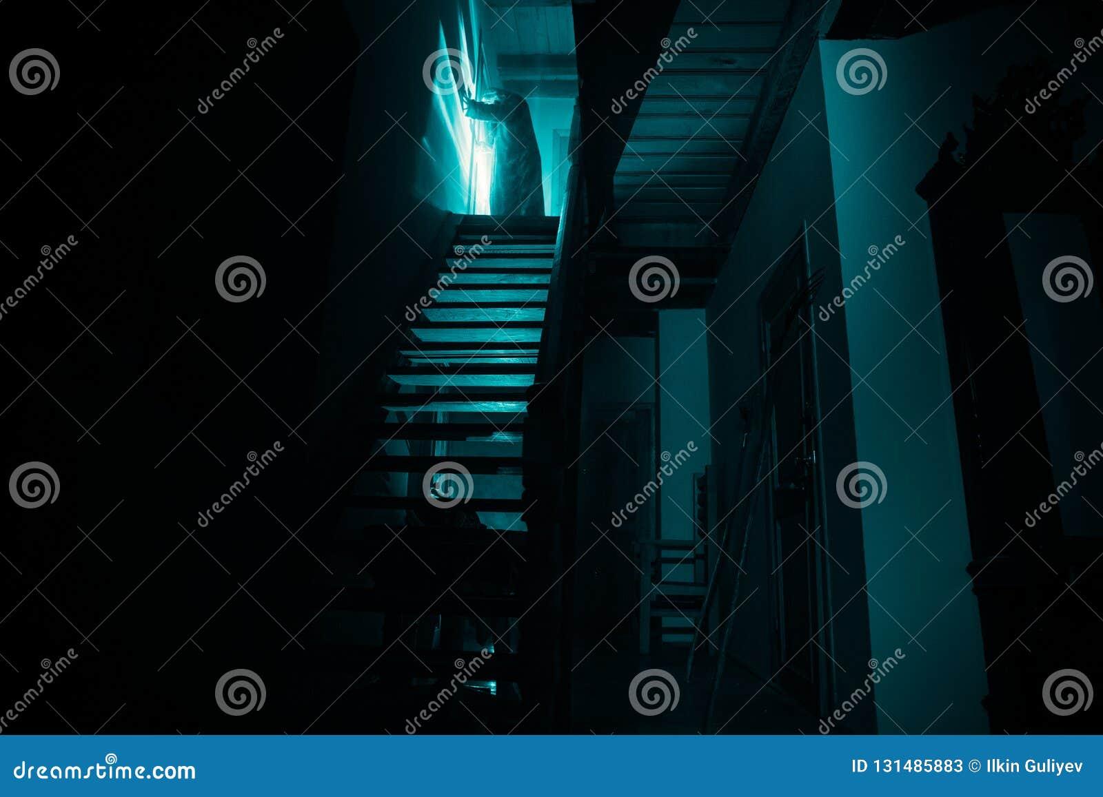 Binnenkant van oud griezelig verlaten herenhuis Silhouet die van verschrikkingsspook zich op kasteeltreden aan de kelderverdiepin