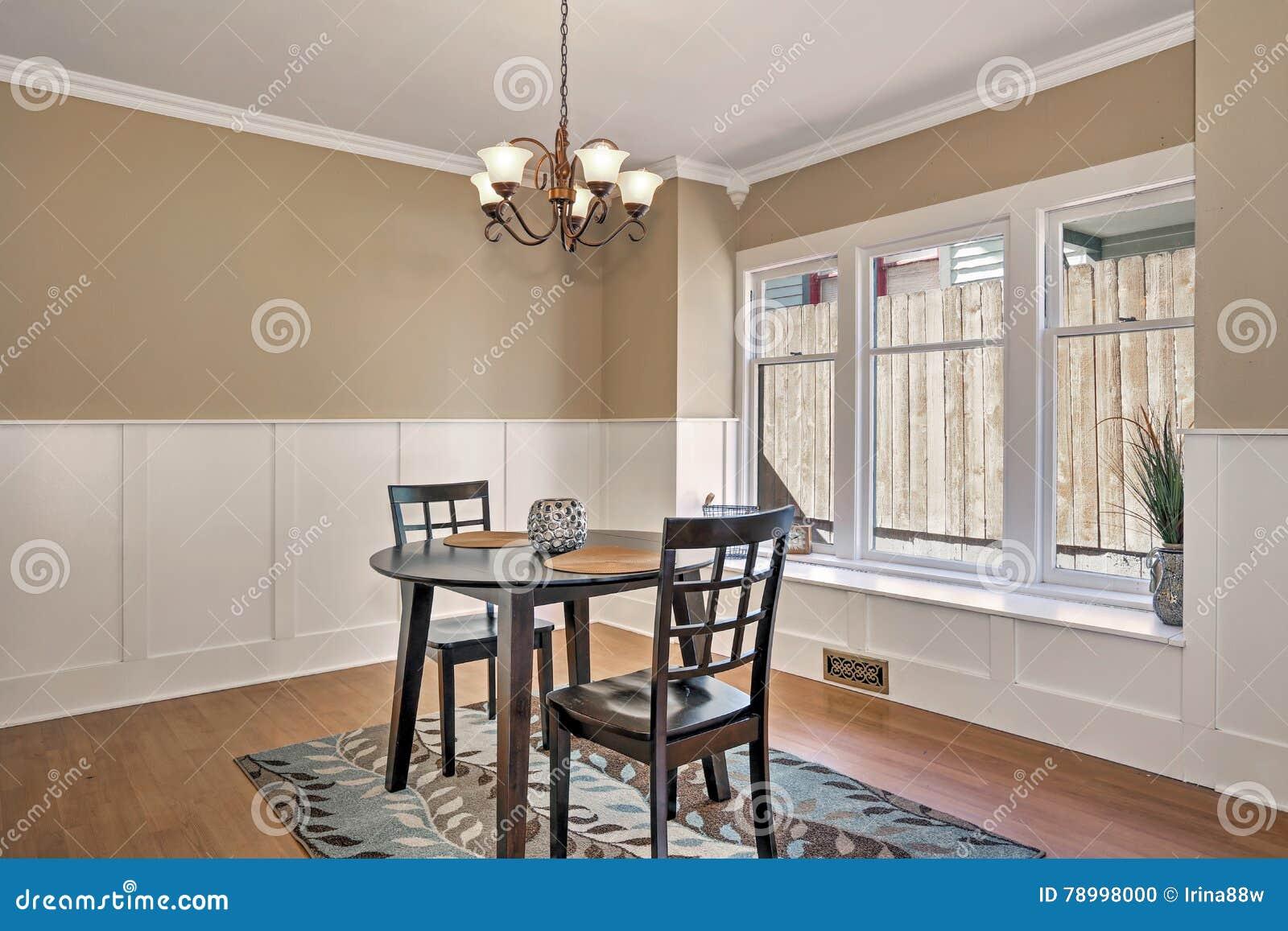 Binnenland van eetkamer met zwarte lijst en twee stoelen stock