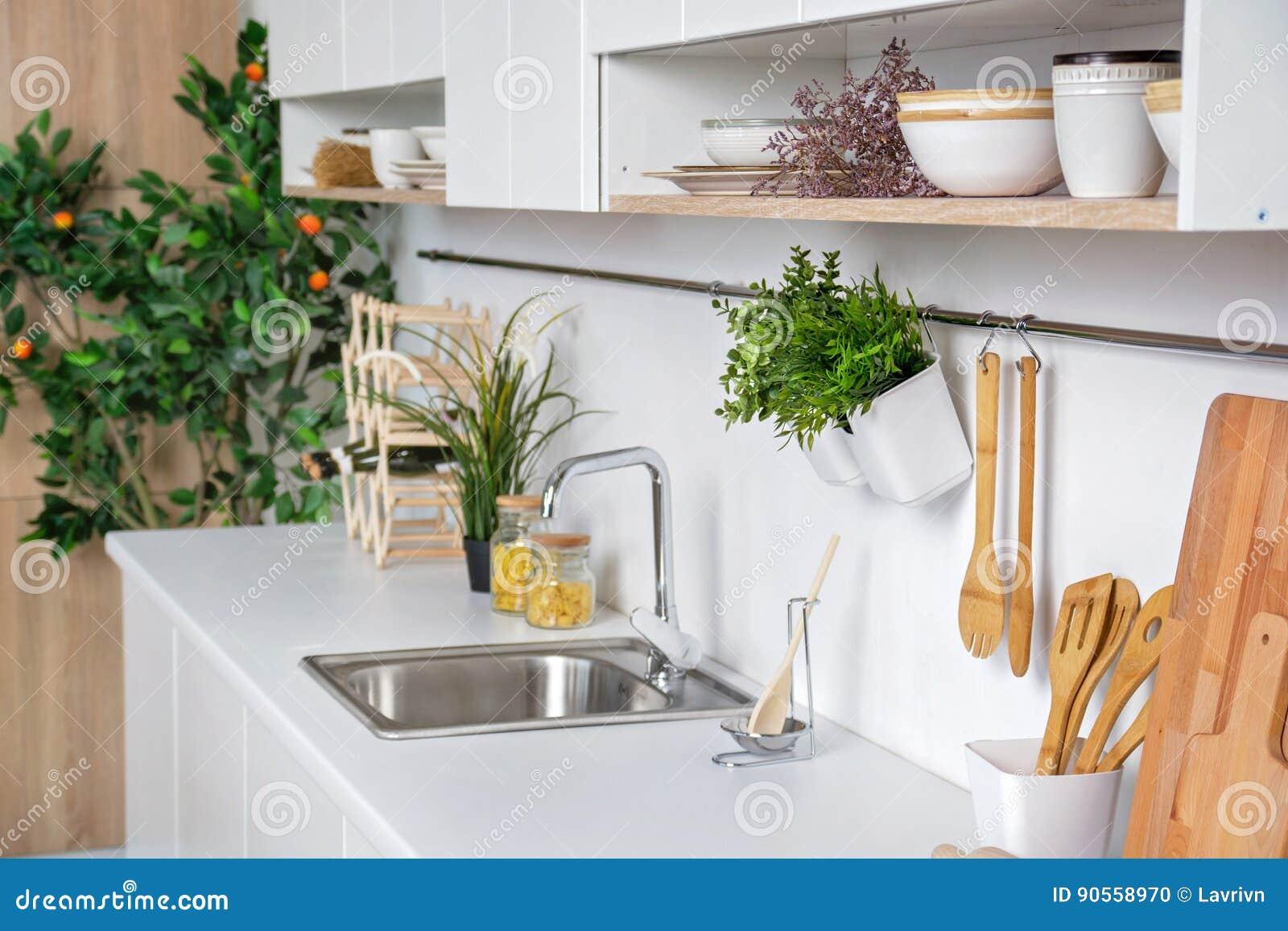 Binnenland van moderne witte keuken met houten keukengerei en