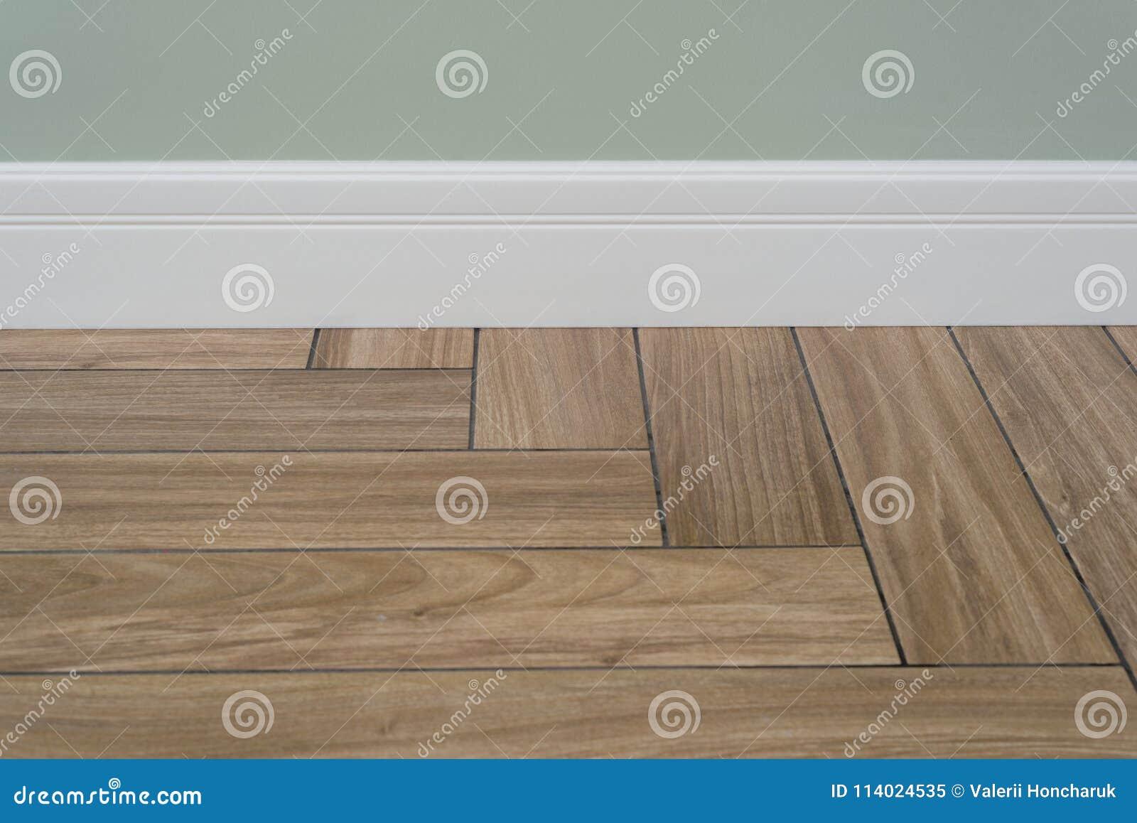 Binnenlands concept Lichte steenmuur, witte plint en tegels die hardhoutbevloering imiteren