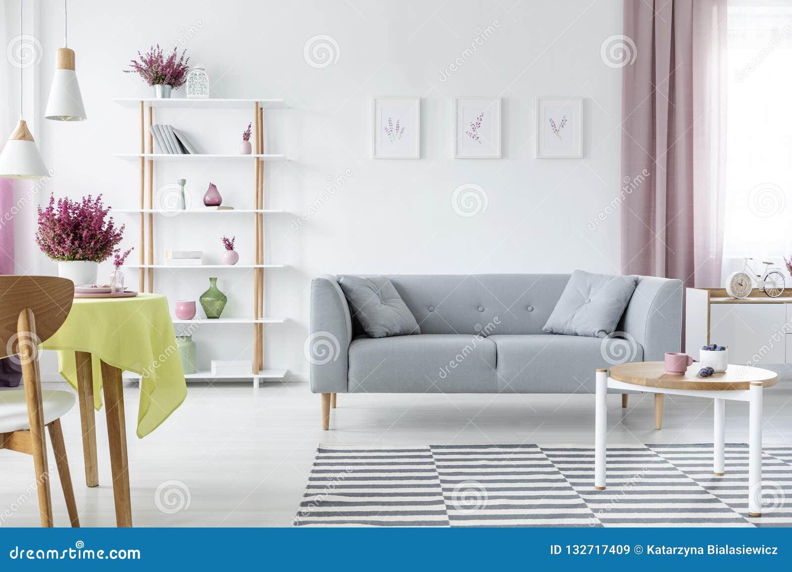 Binnenlands ontwerp met comfortabele Skandinavische laag, houten koffietafel, gestreepte deken en grafiek op de vloer, echte foto