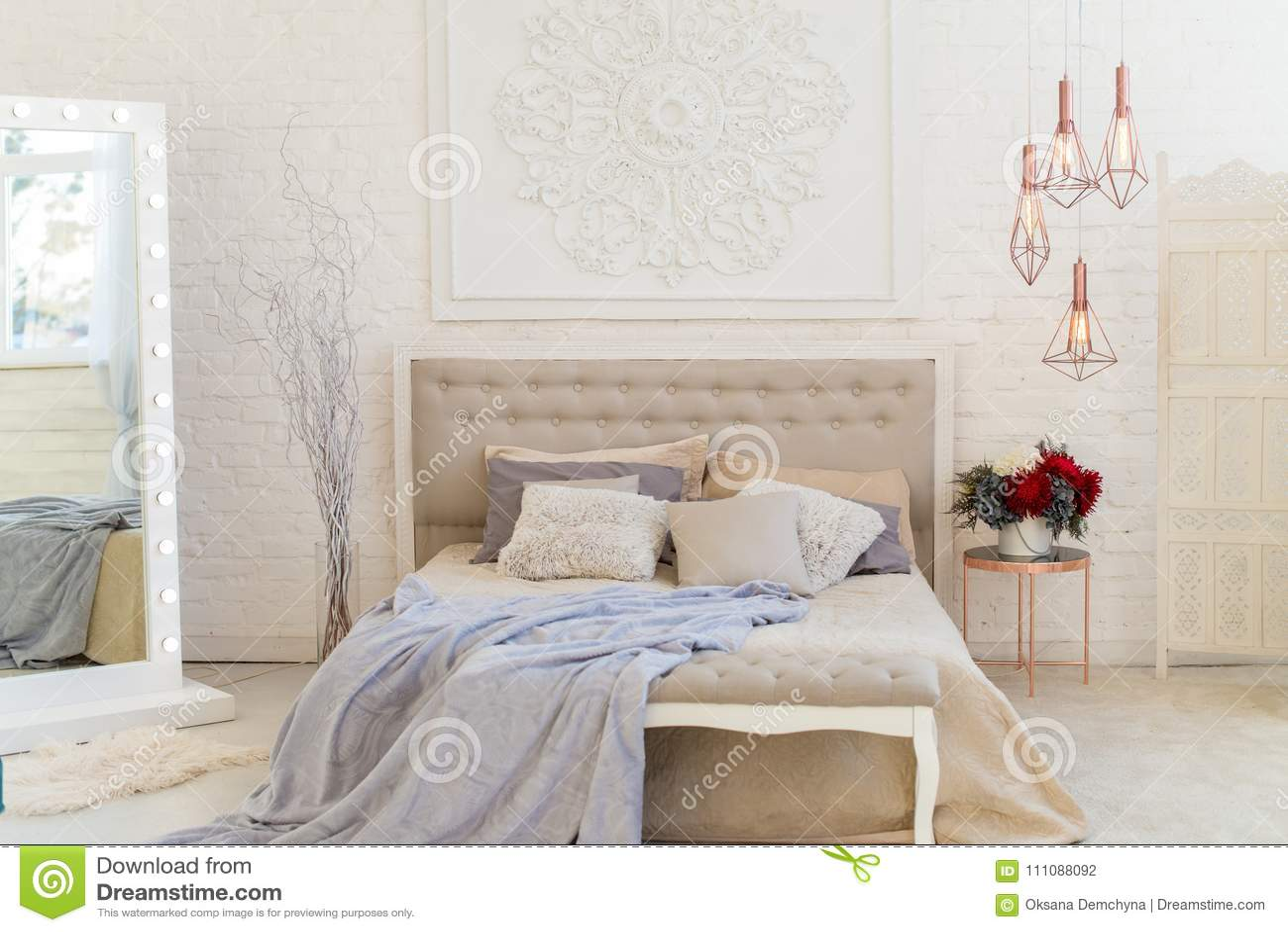 binnenlandse slaapkamer in pastelkleur lichte kleuren groot comfortabel tweepersoonsbed in elegante klassieke slaapkamer