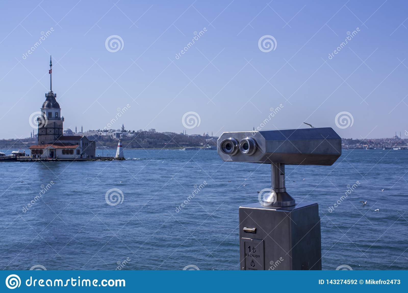 Binoculars by the sea overlooking the Bosphorus and the Asian part of Istanbul. Maiden`s Tower on the left side