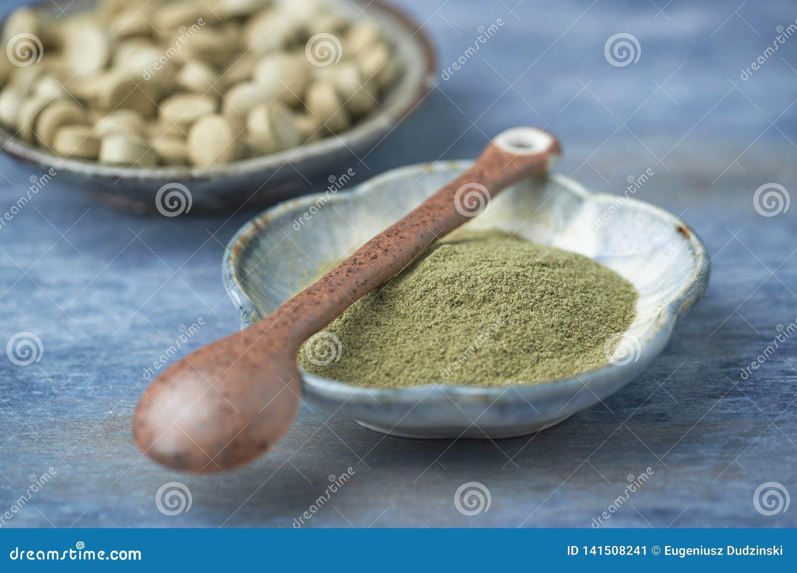 Bio pó e tabuletas verdes da GRAMA de CEVADA Conceito para um suplemento dietético saudável