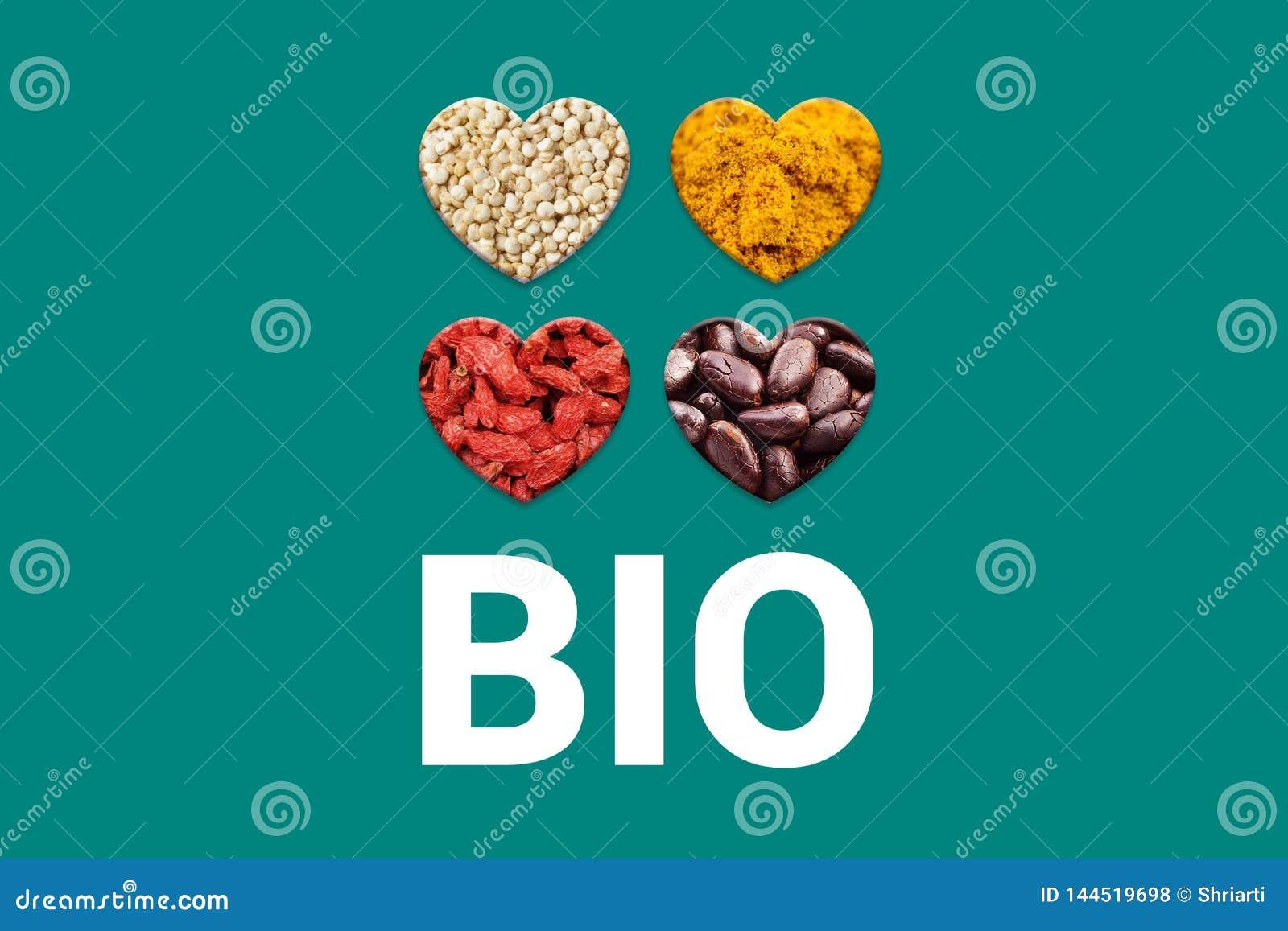 Bio texto blanco en fondo y corazones de la turquesa con las semillas del cacao, granos blancos de la quinoa, bayas secadas del g