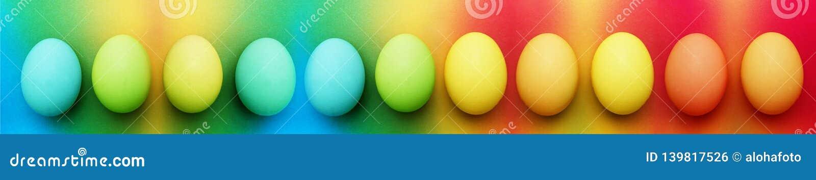 Biologiskt organiskt blått äpple för turkos elva - gröna gula easter ägg på en regnbågebakgrund