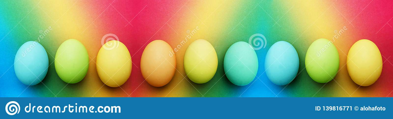 Biologiskt organiskt blått äpple för turkos nio - gröna gula easter ägg på en regnbågebakgrund