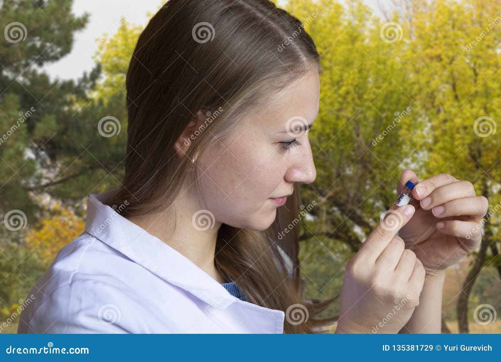 Biologiste de jeune femme dans le liquide de versement de manteau blanc du tube à essai dans le pot avec le sol Pousses à l arriè