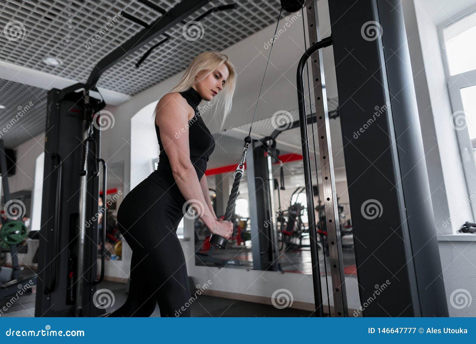 Bionda attraente della giovane donna in abiti sportivi che fanno gli esercizi di forza per le mani per mezzo del simulatore moder