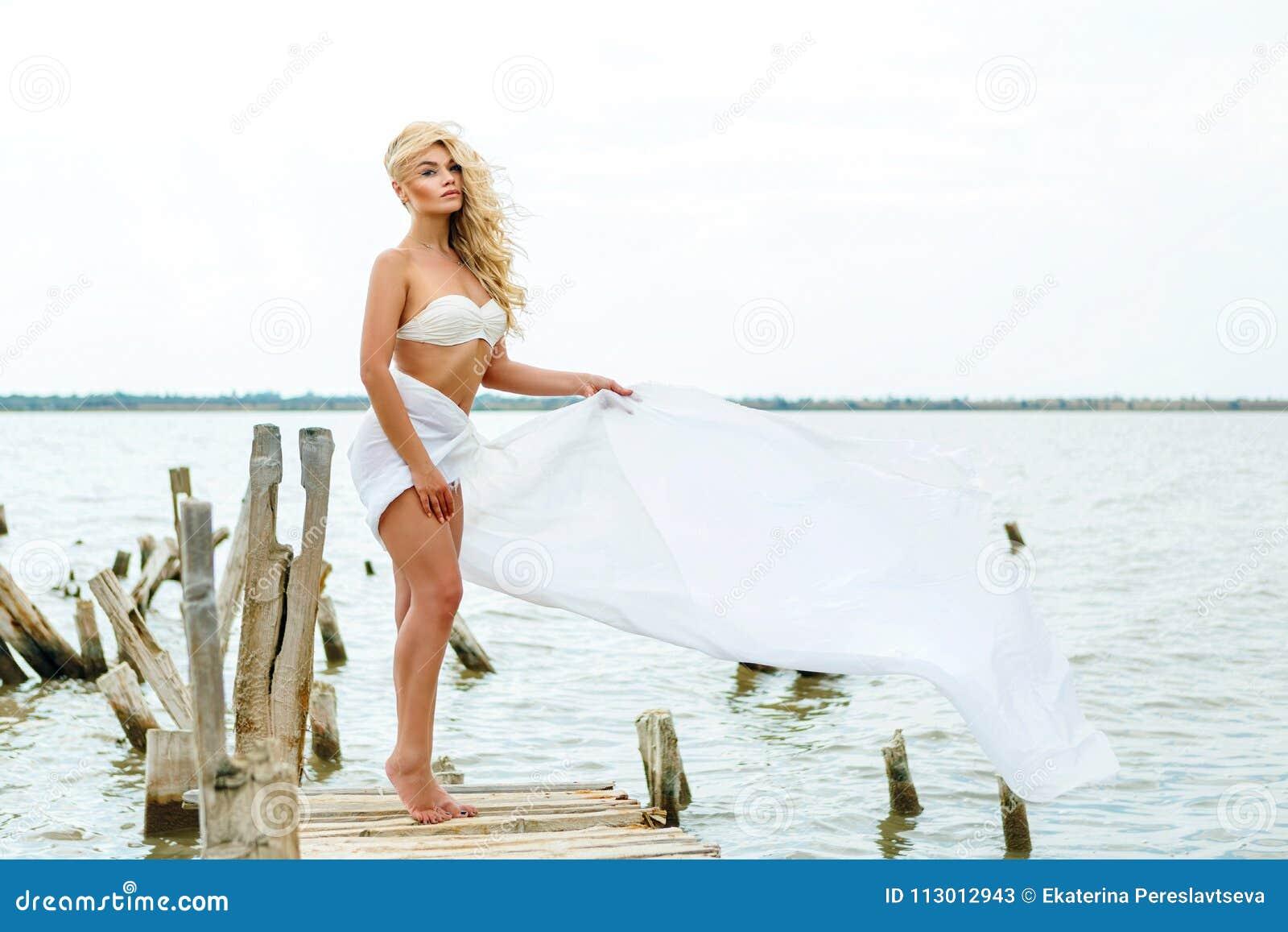 Bionda in un costume da bagno bianco, stante sui precedenti del lago nel vento, nel resto e nel rilassamento