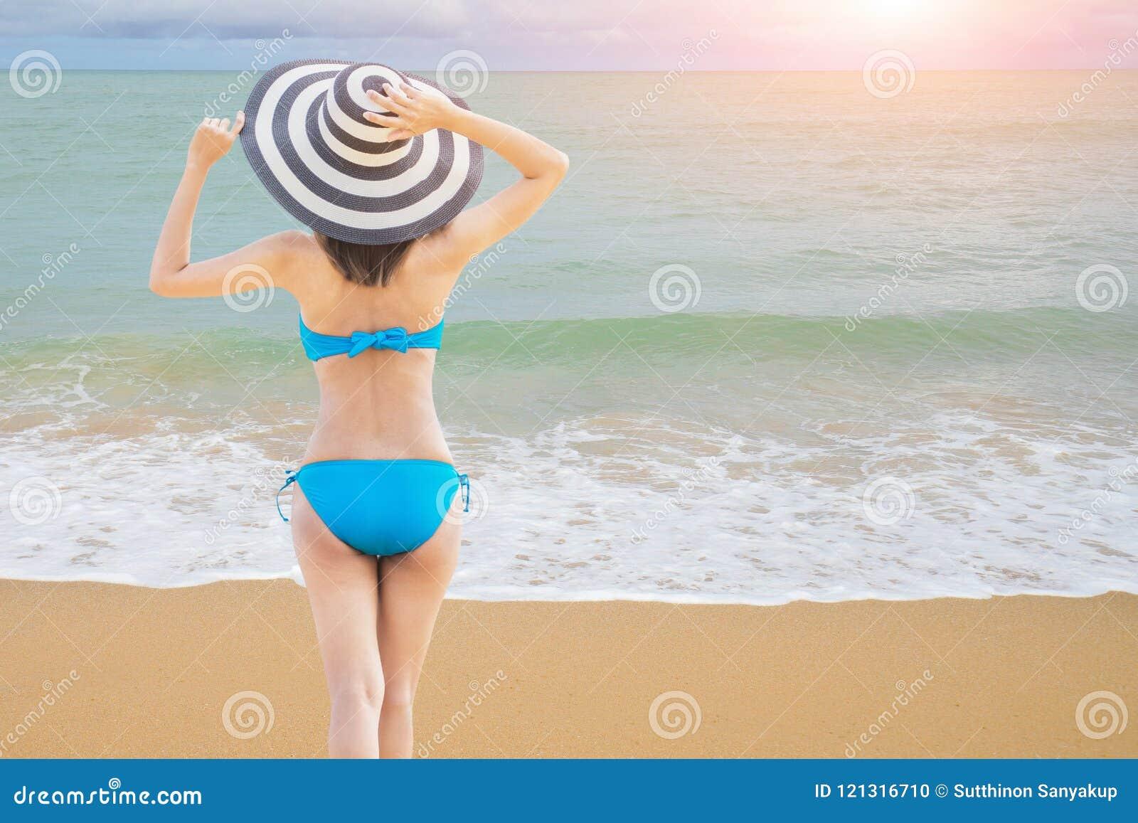 Biquini vestindo da mulher  sexy  bonita nova e relaxamento no Sandy Beach branco perto das ondas do azul na praia tropical