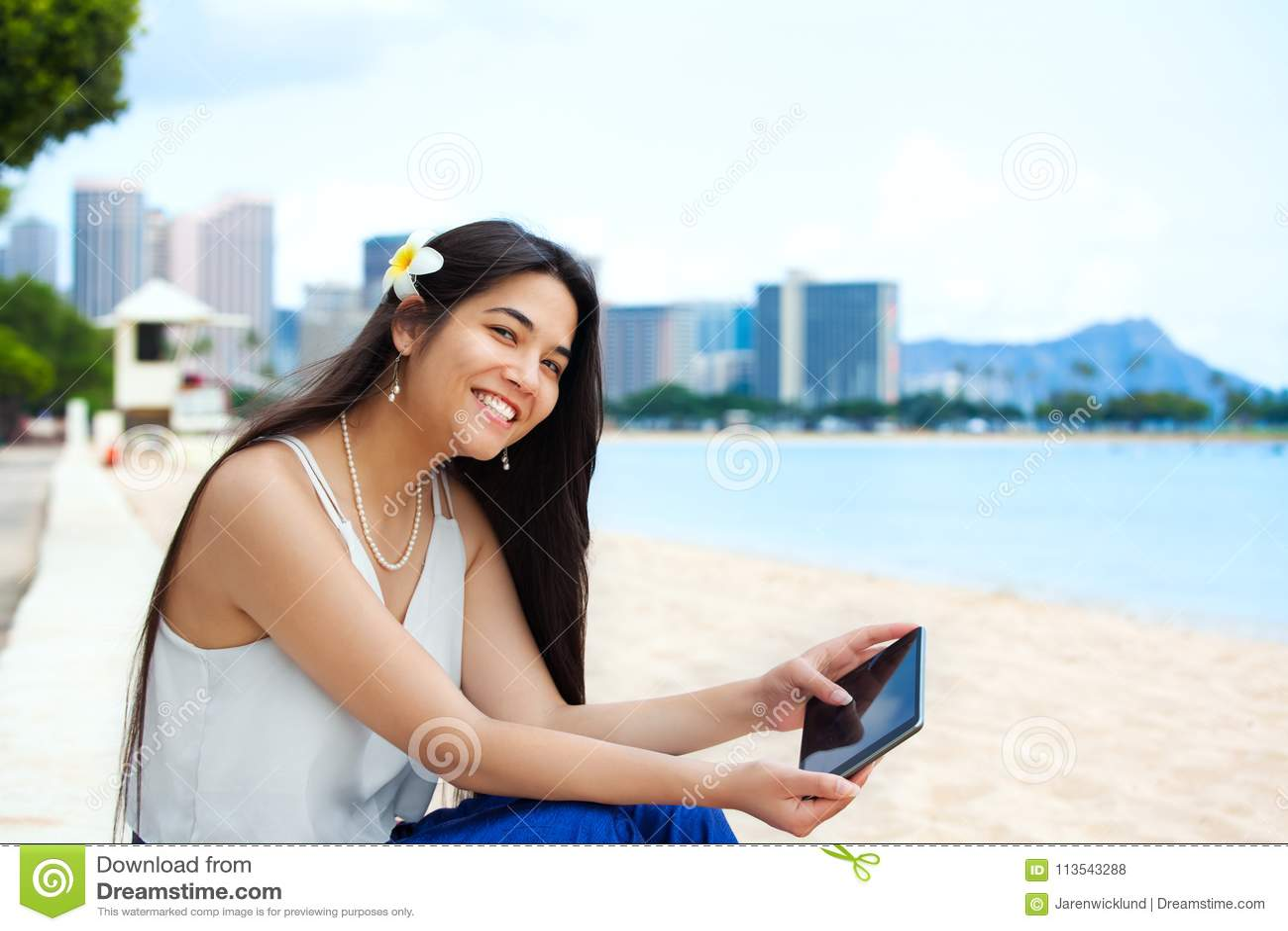 Biracial предназначенная для подростков девушка на пляже используя планшет, Waikiki, Hono