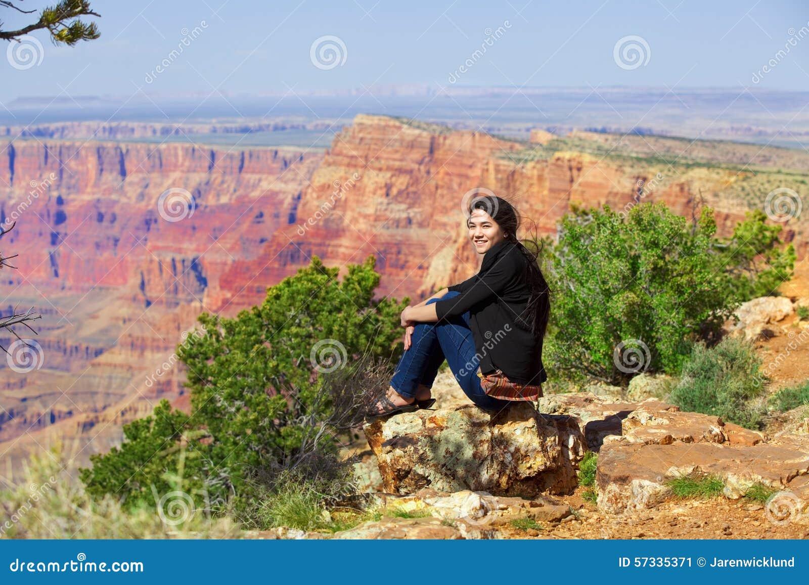 Biracial предназначенная для подростков девушка сидя вдоль уступа утеса на гранд-каньоне