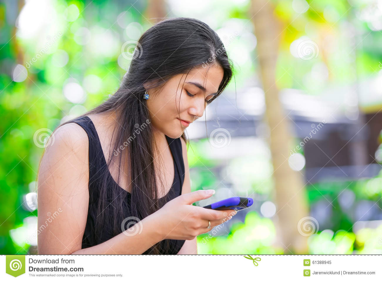 biracial teen girl talking on cell phone outdoors stock