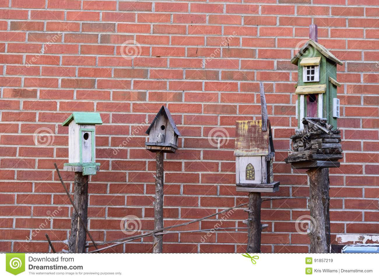 4 birdhouses with brick background