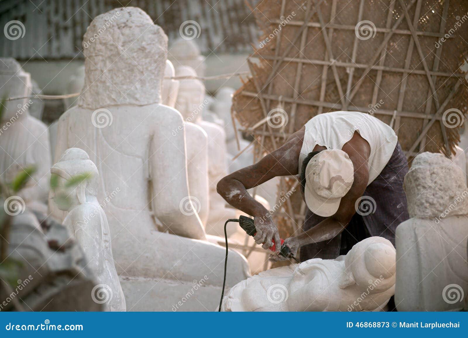 Birmański mężczyzna rzeźbi wielką marmurową Buddha statuę