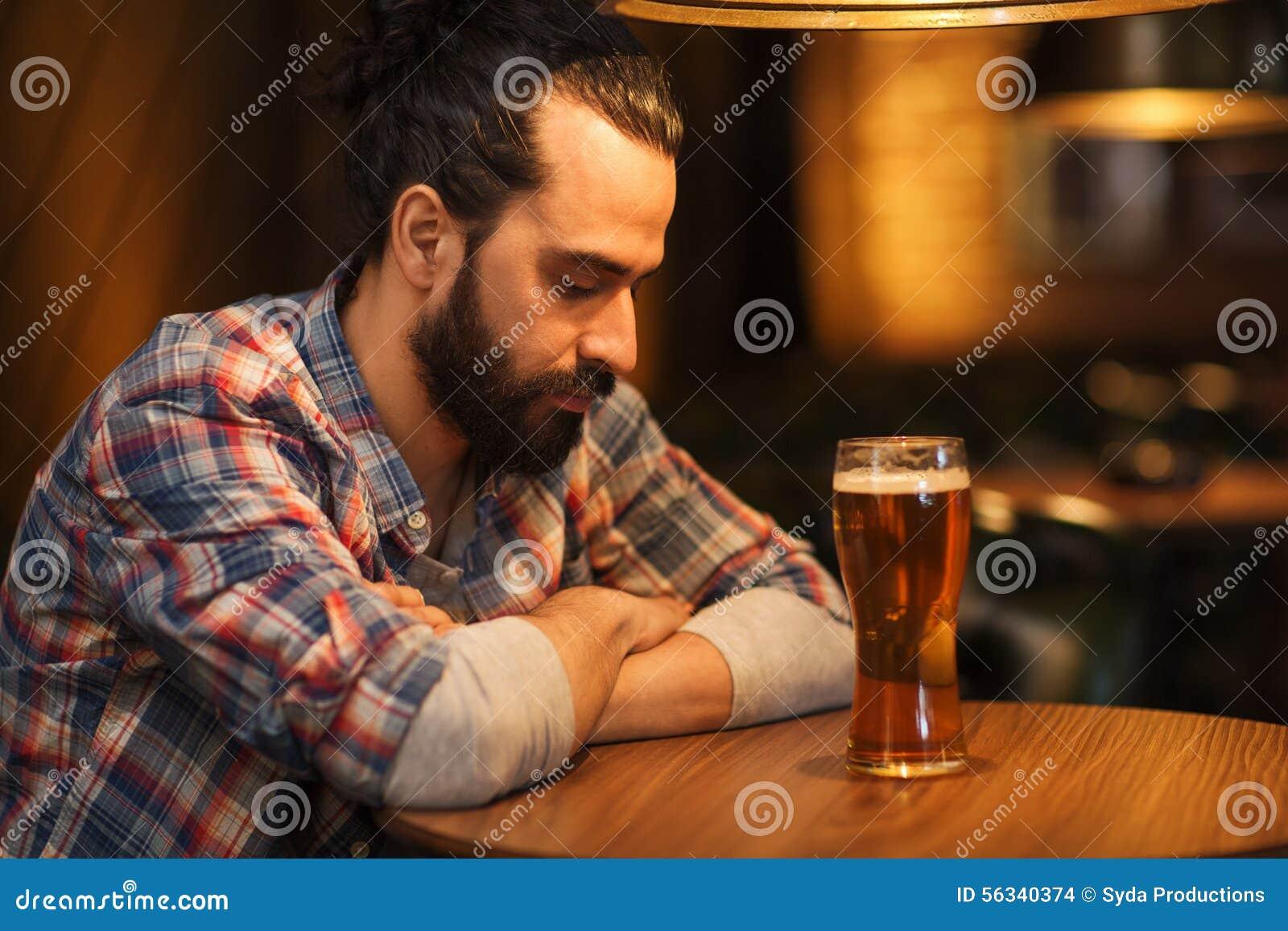 Birra bevente dell uomo solo infelice alla barra o al pub