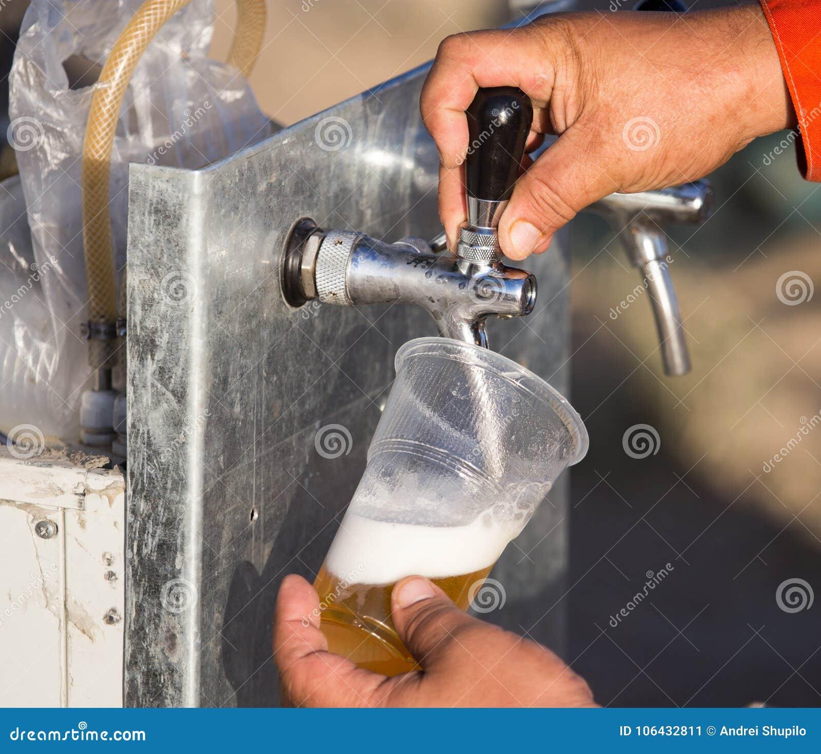 Birra fresca in una tazza di plastica nella mano