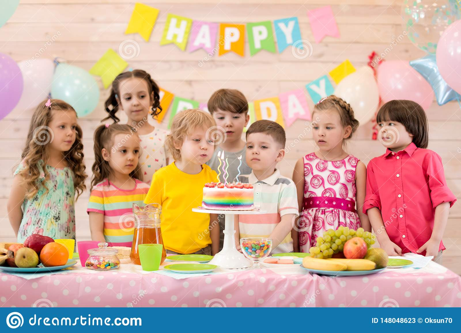 Birthday boy blows festival candles on cake together with friends