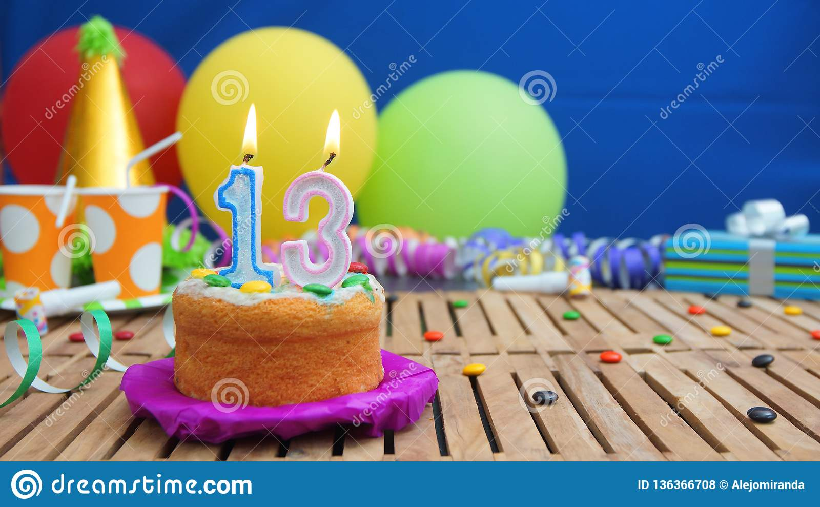 Birthday 13 cake with candles on rustic wooden table with background of colorful balloons, gifts, plastic cups and candies