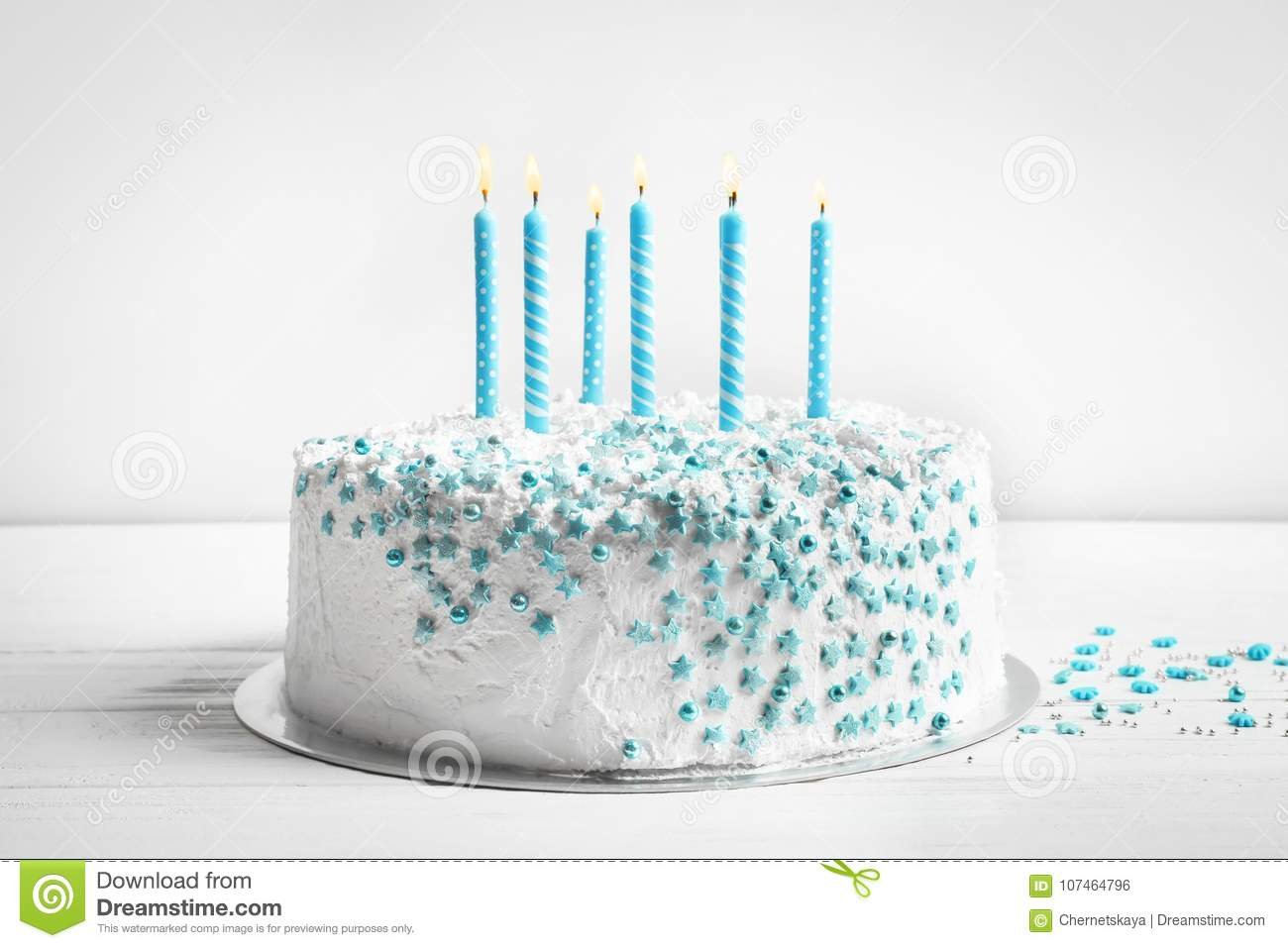 Birthday cake with candles on table against wall