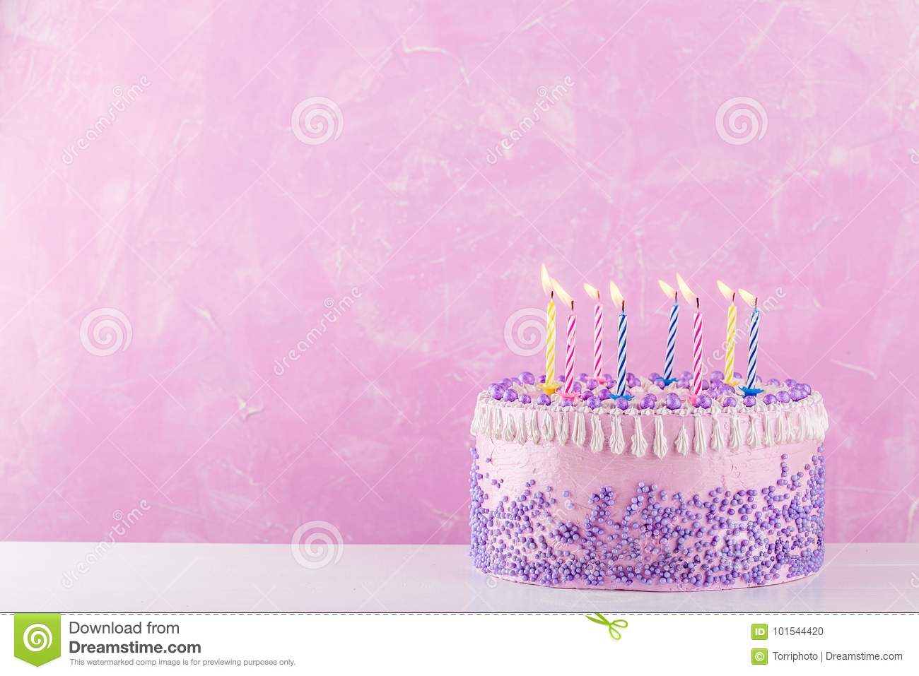 Birthday Cake With Purple Sprinkles And Colorful Candles Over Pink Background