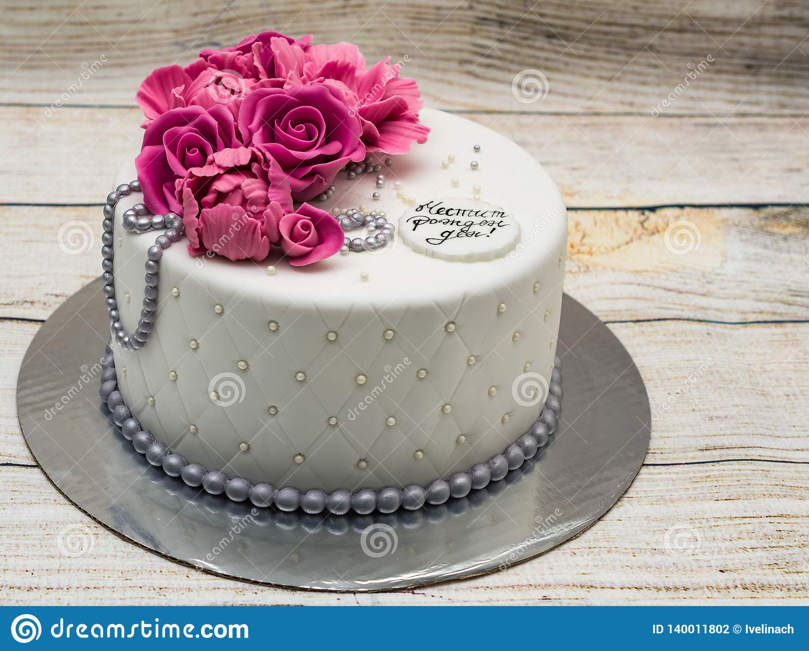 Birthday cake with fondant flowers - roses and peonies and silver pearls. Inscription `Happy Birthday`