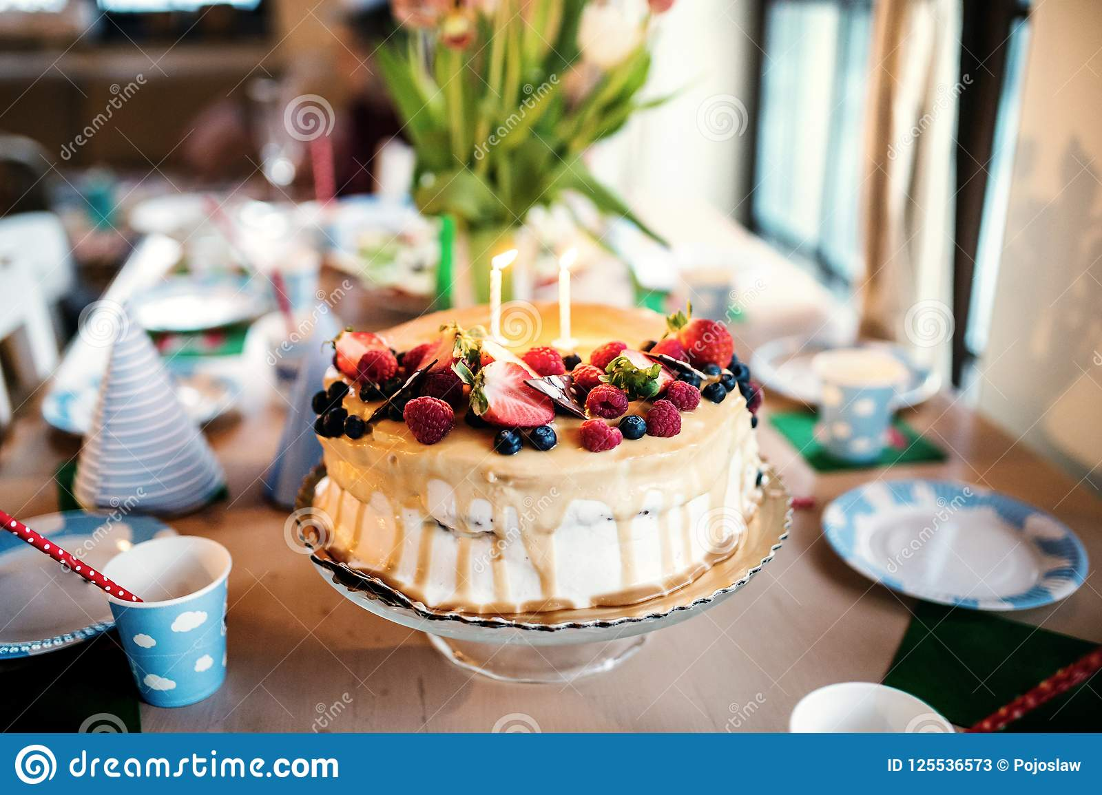 A Birthday Cake On Glass Stand And Vase With Tulips The Table