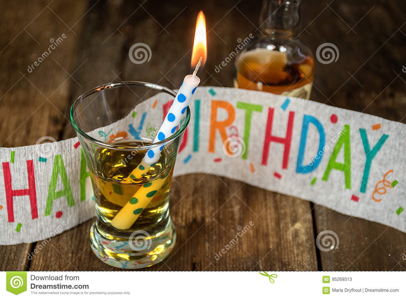 Birthday Candle And Whiskey In Shot Glass With Banner On Rustic Wood