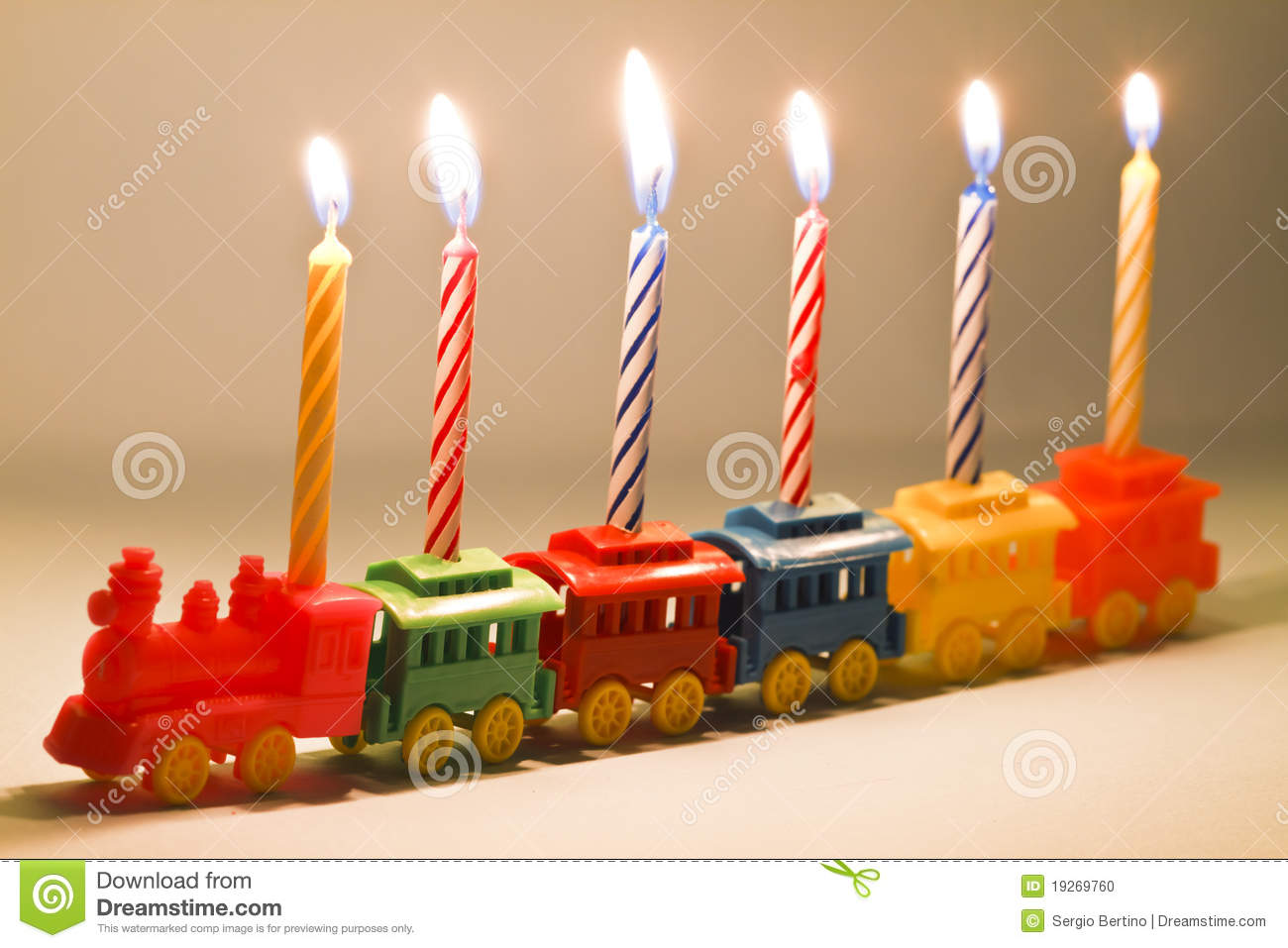 Plastic Toy Train Carrying Six Lit Striped Birthday Candles