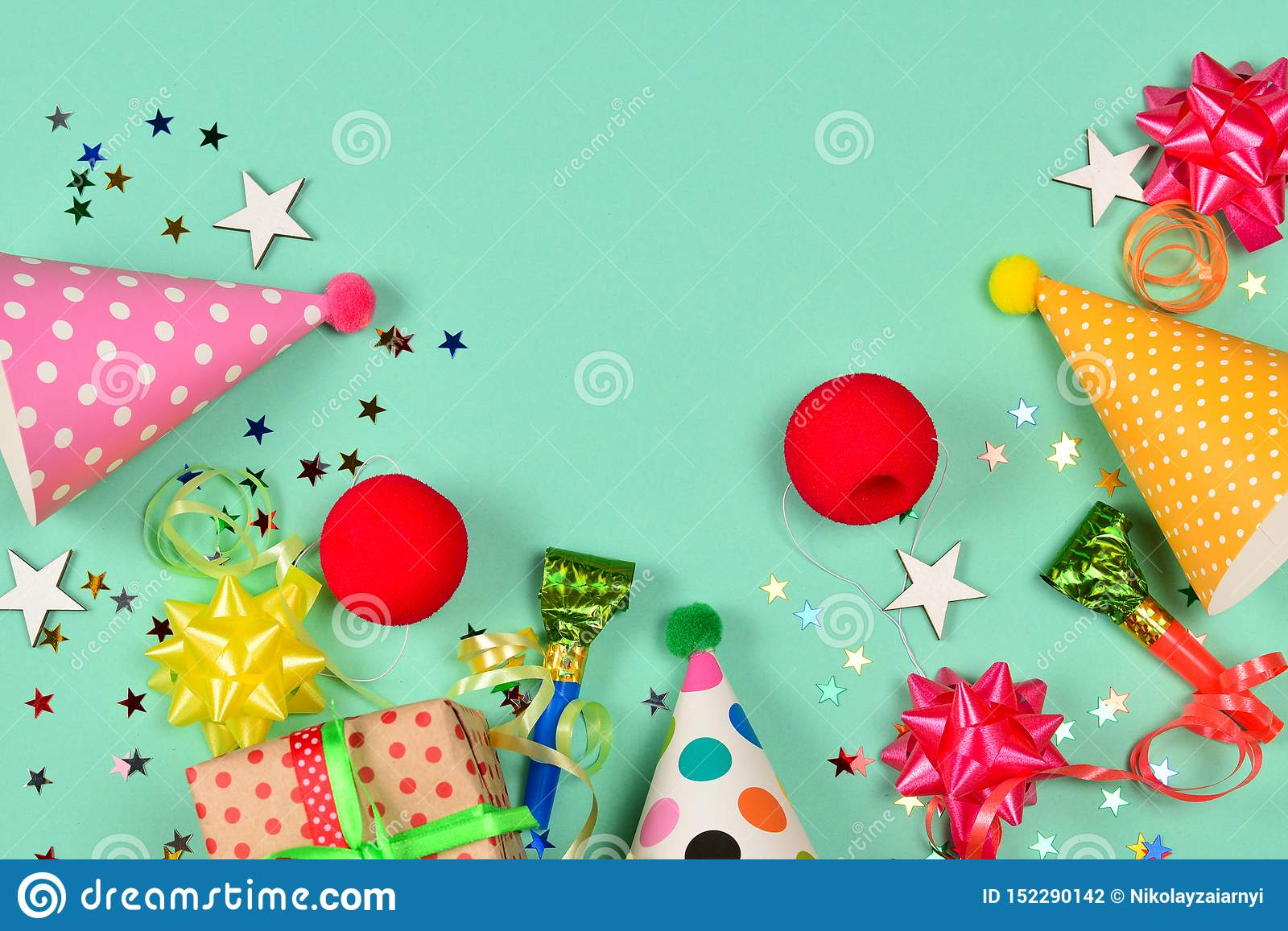 Birthday caps, present, confetti, ribbons, stars, clown noses on a green background. Space for text or design