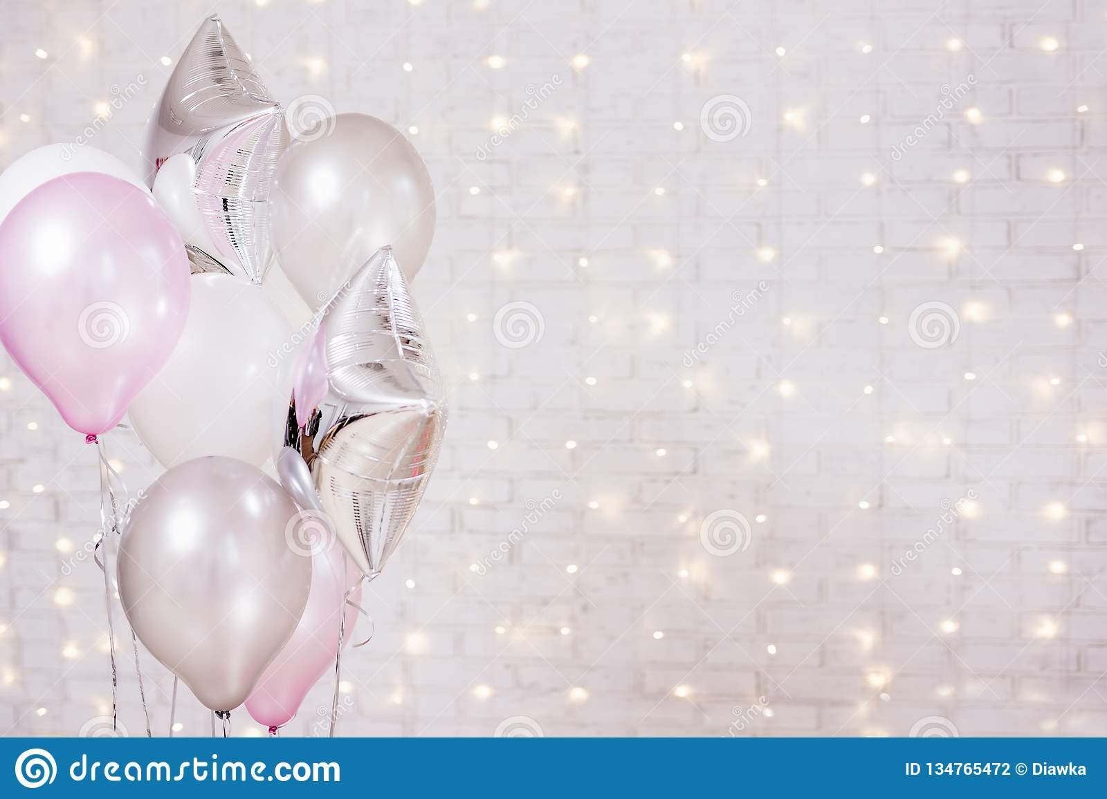 Birthday and christmas concept - close up of air balloons over brick wall background with lights