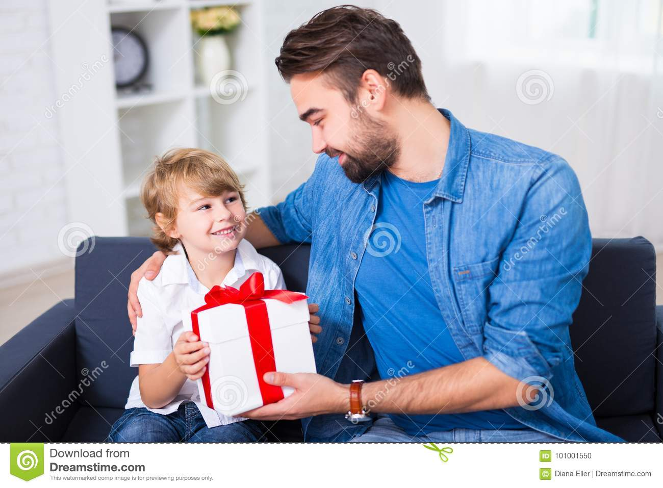 Birthday or christmas concept - father giving gift to his happy