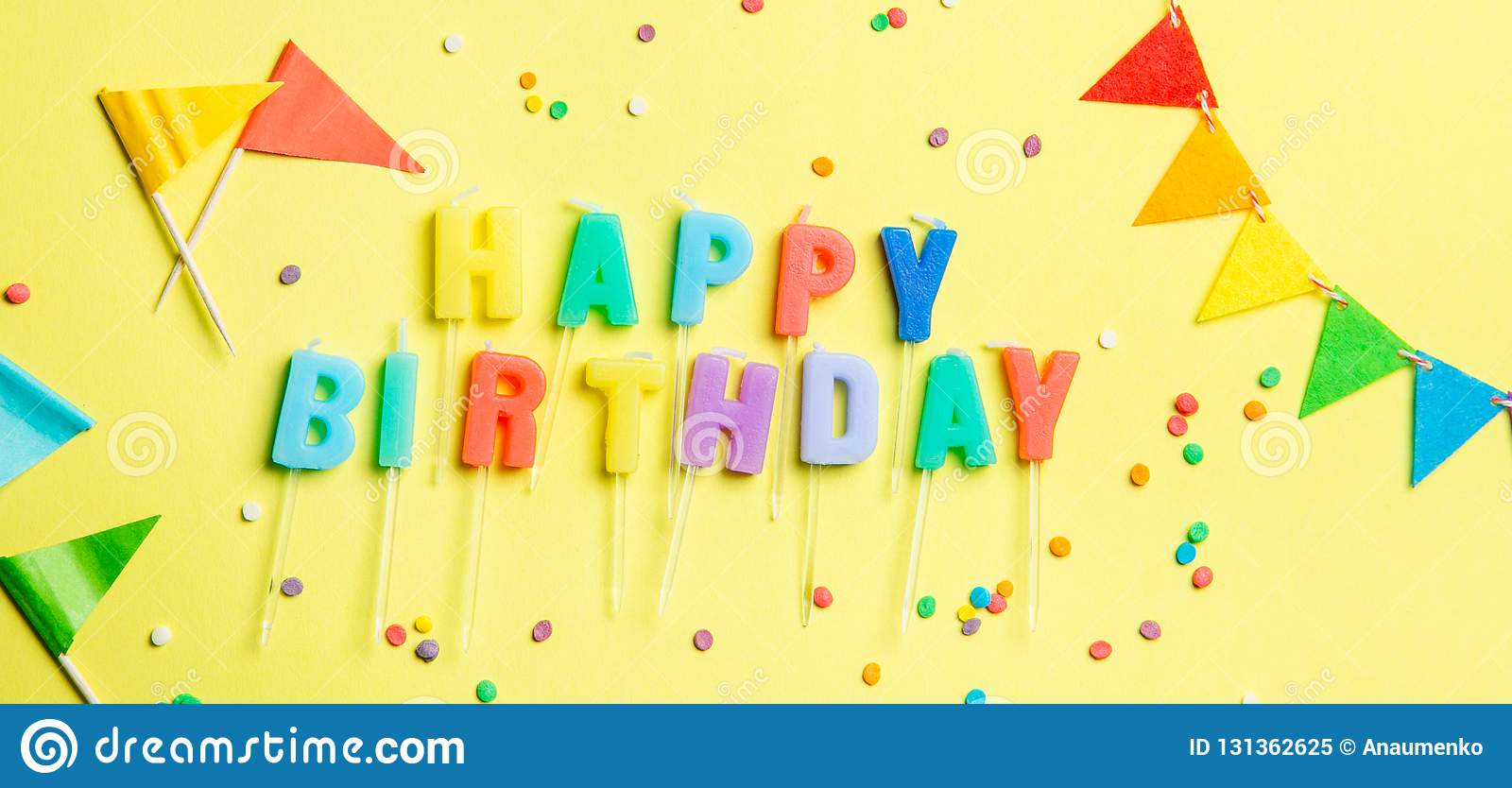 Birthday concept - candles with letters `happy birthday` and confetti