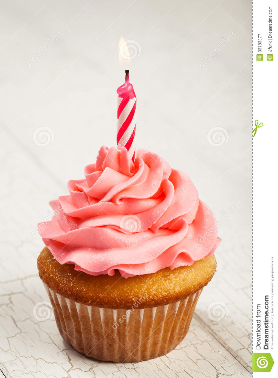 Delicious birthday cupcake with pink buttercream icing and lit candle ...