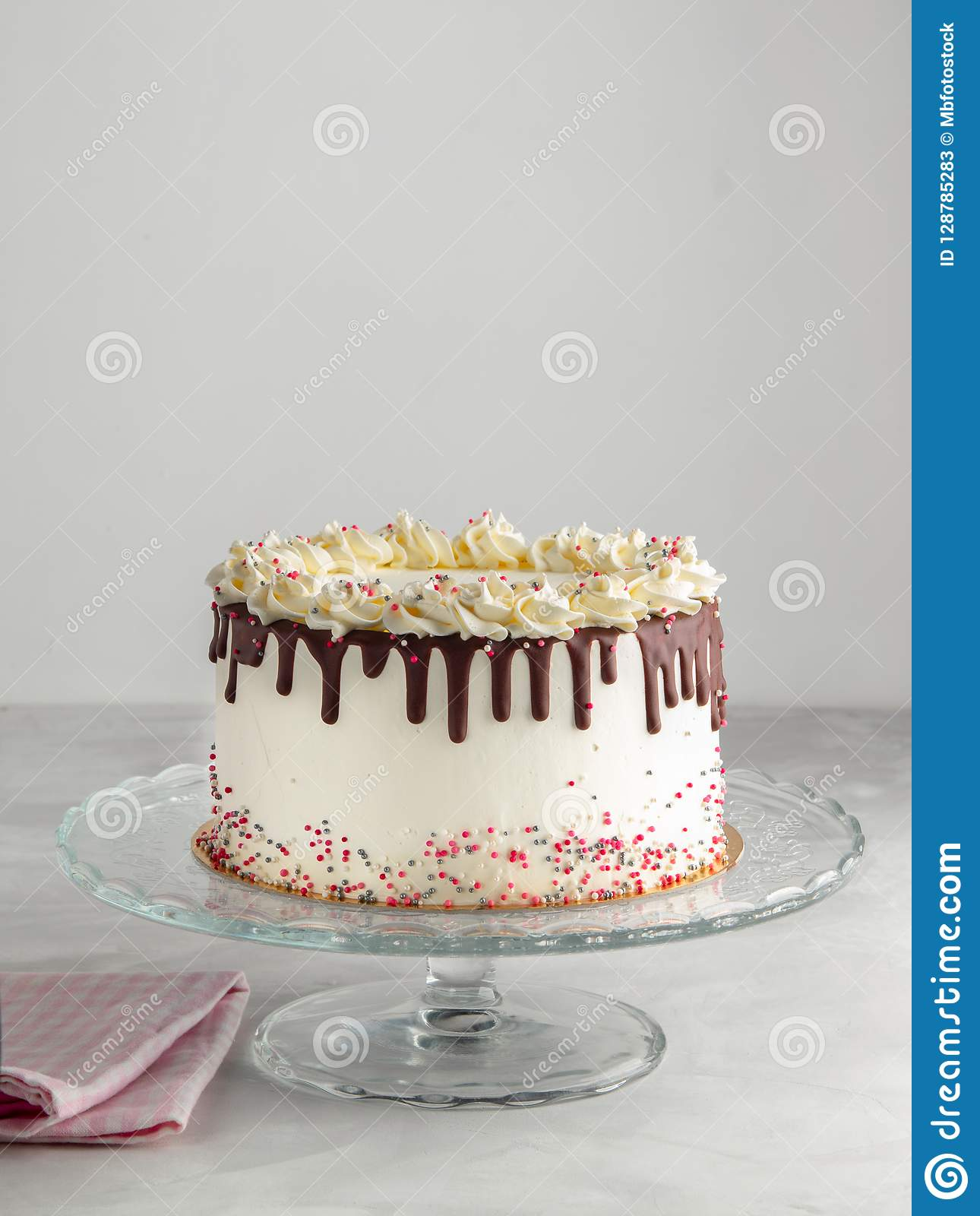 Birthday Drip Layered Cake with chocolate ganache and sprinkles on a white background with party decor. Horizontal. Copy space. Ce