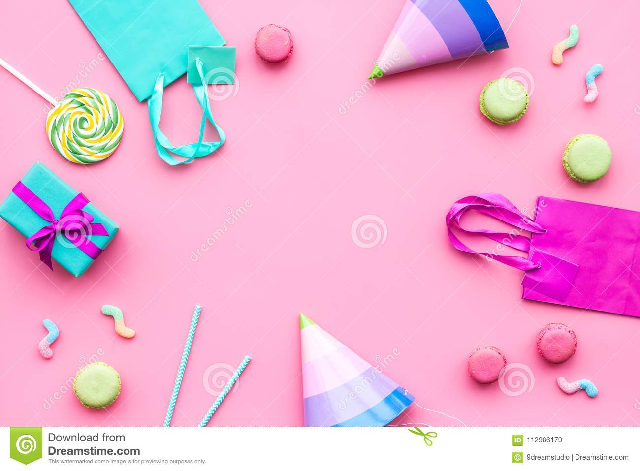 Birthday party accessories. Party hat, sweets, paper bag for gift on pink background top view copy space mockup
