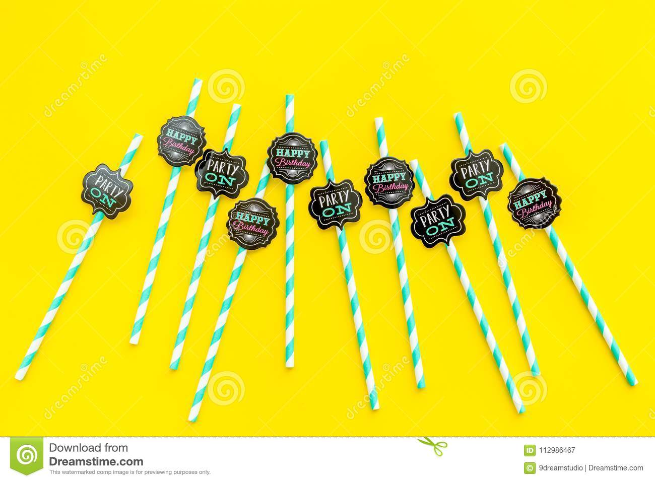 Birthday party background. Lettering Party on and happy birthday on drink straws on yellow top view copy space