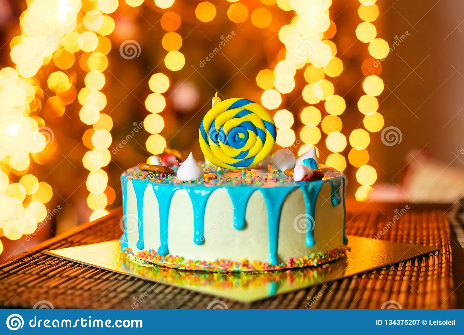 Birthday white cake with sweets and candle for little baby boy and decorations for cake smash