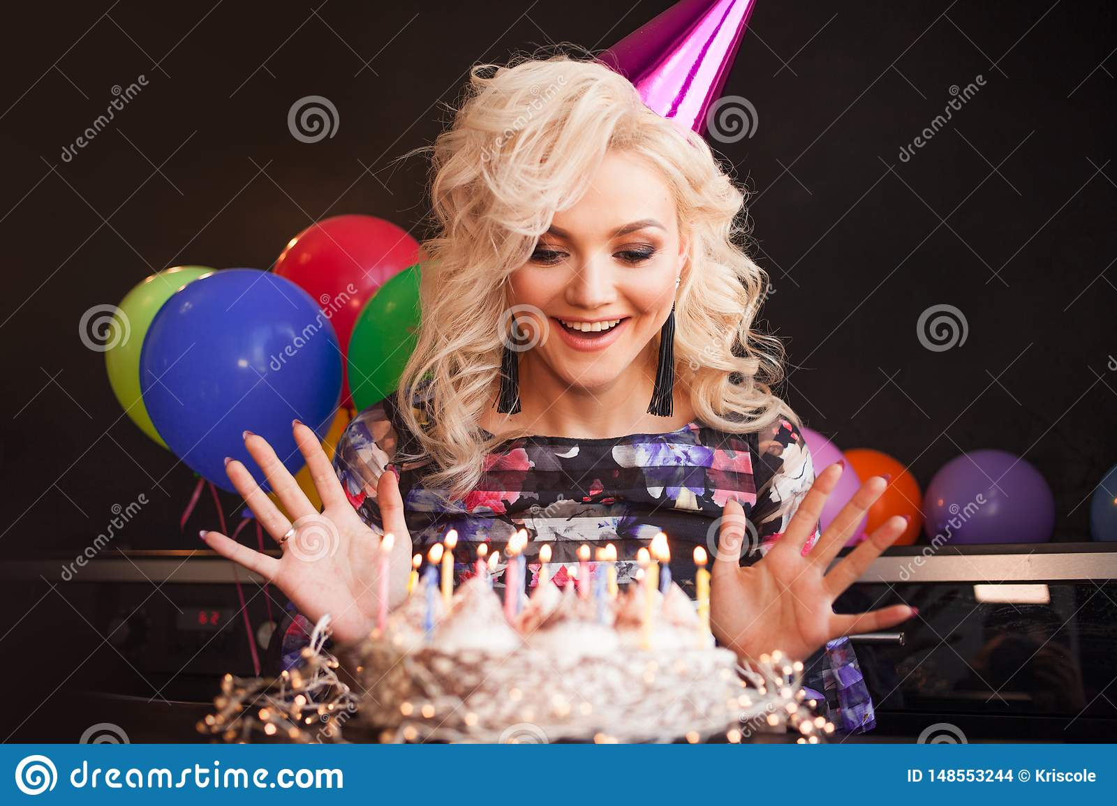 Birthday, a young woman blows out the candles on her birthday cake.