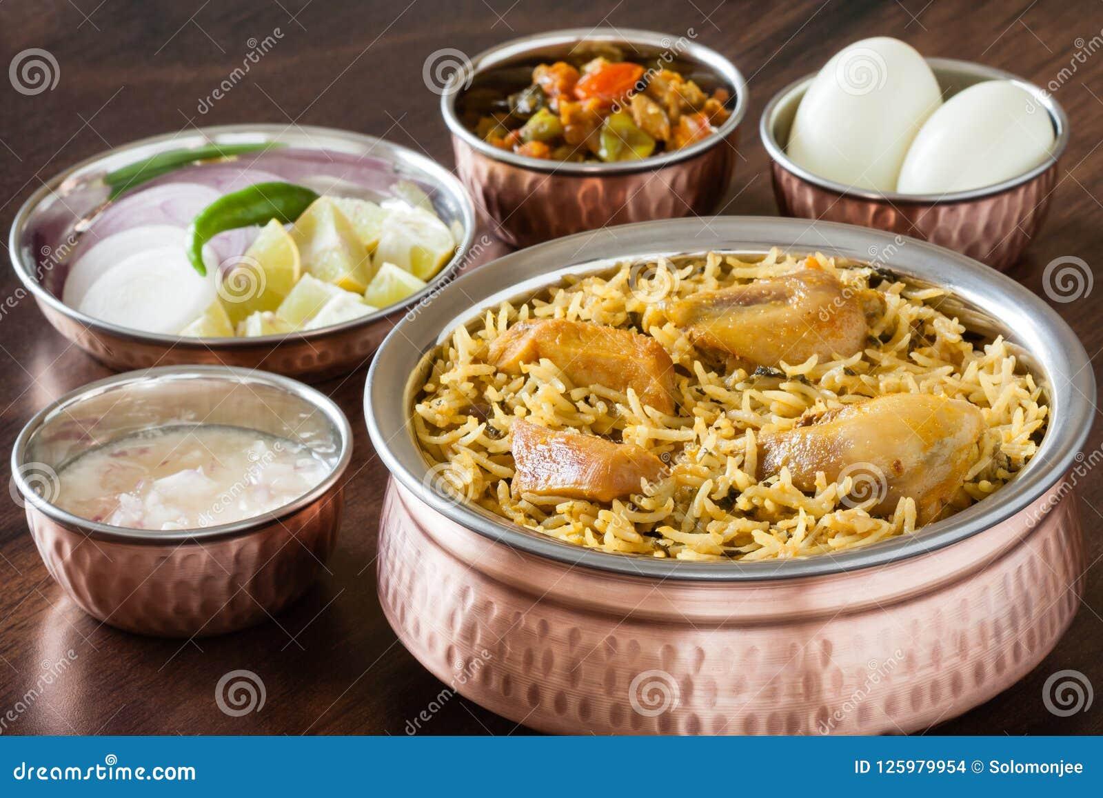 Biryani del pollo con i lati tradizionali