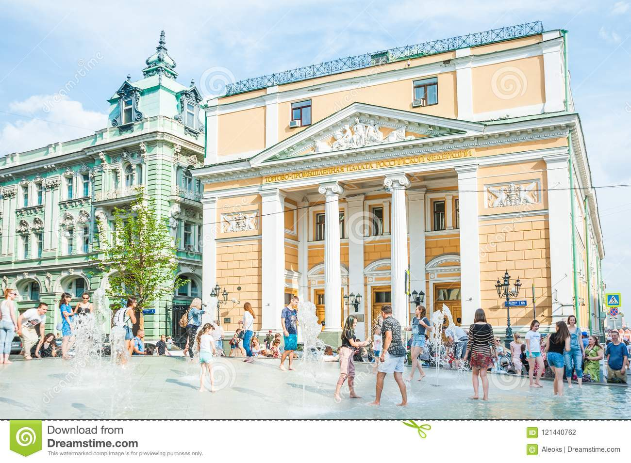 Birzhevaya square. The Chamber of Commerce and Industry of the Russian Federation. People splash in the fountain in hot weather
