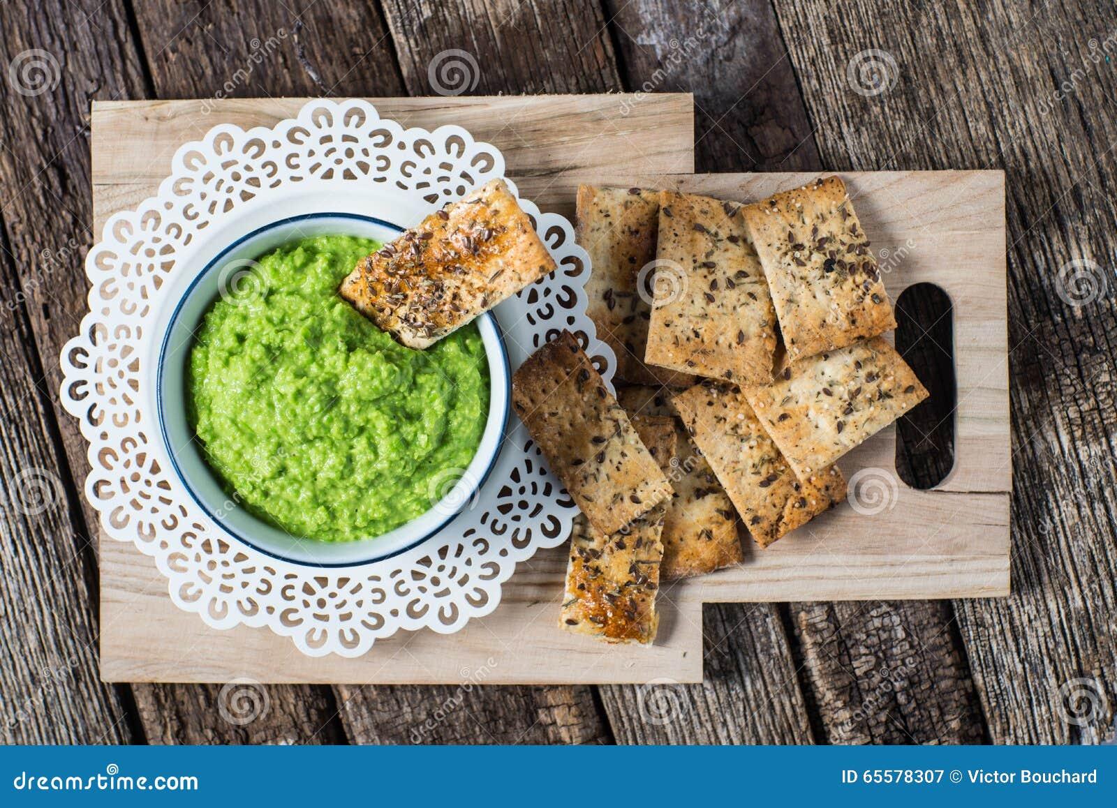 Biscoitos do artesão com propagação do hummus da ervilha verde