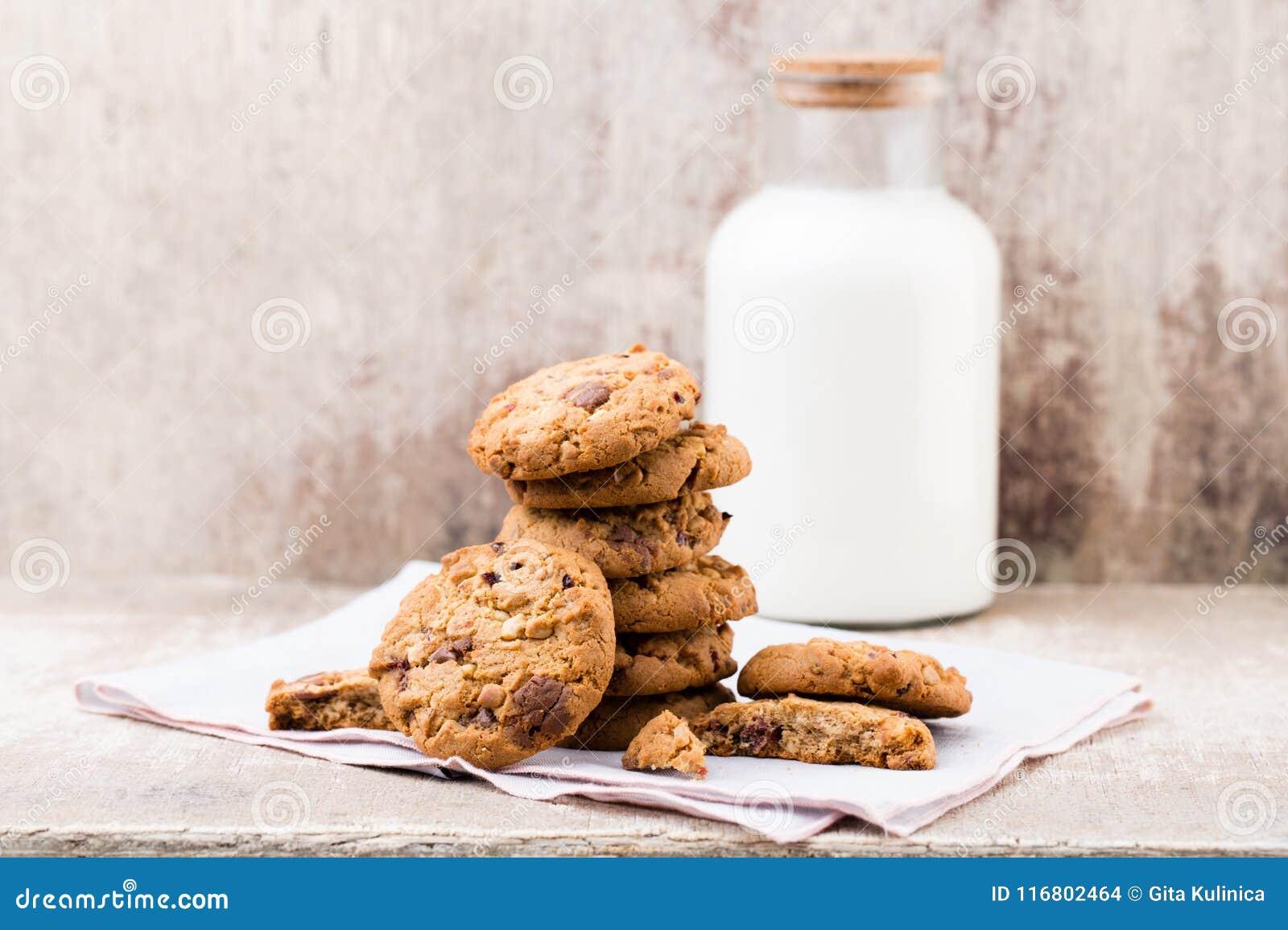 Biscotti del chip della farina d avena del cioccolato con latte sui tum di legno rustici