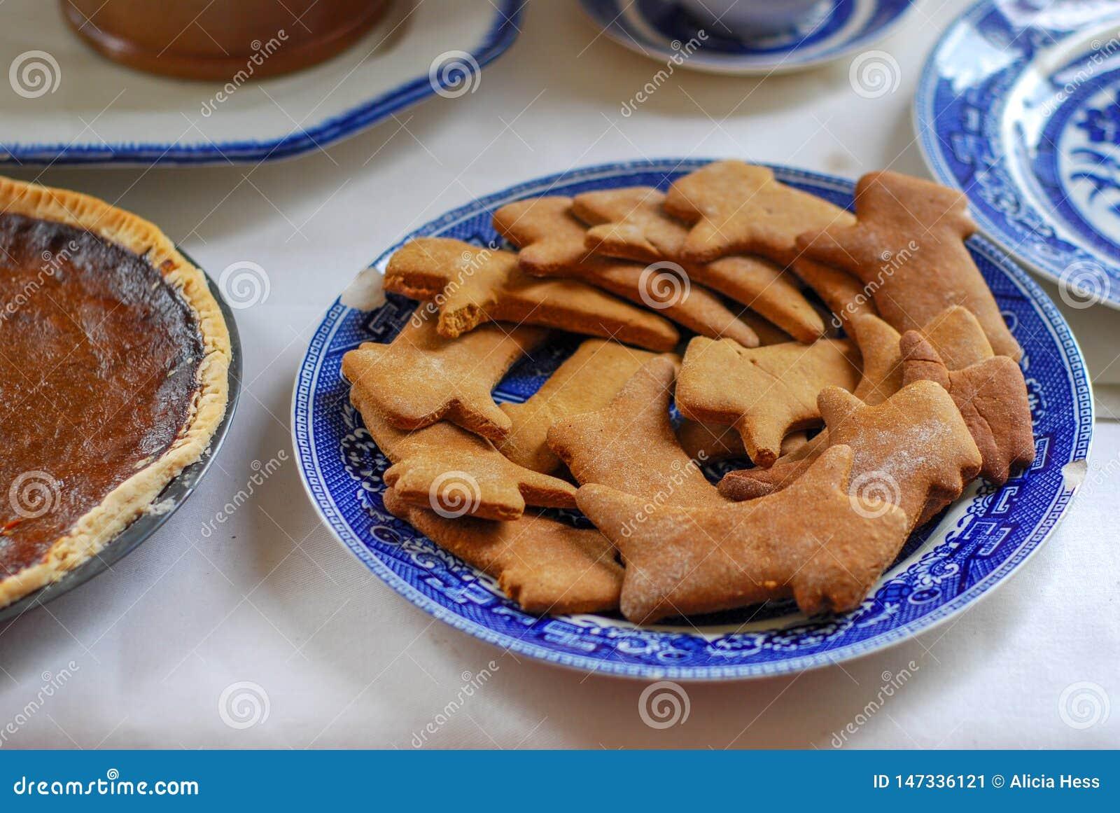 Biscotti deliziosi del pan di zenzero su un piatto antico blu