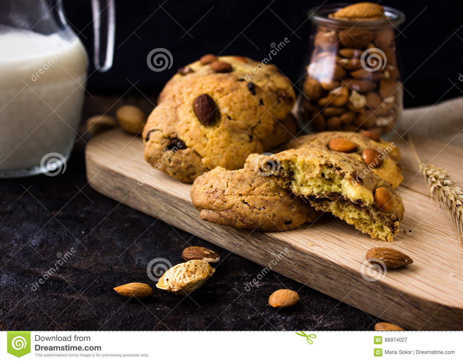 Biscotti di biscotto al burro americani con le gocce di cioccolato e una brocca di latte e di mandorle Fondo scuro di lerciume Lu