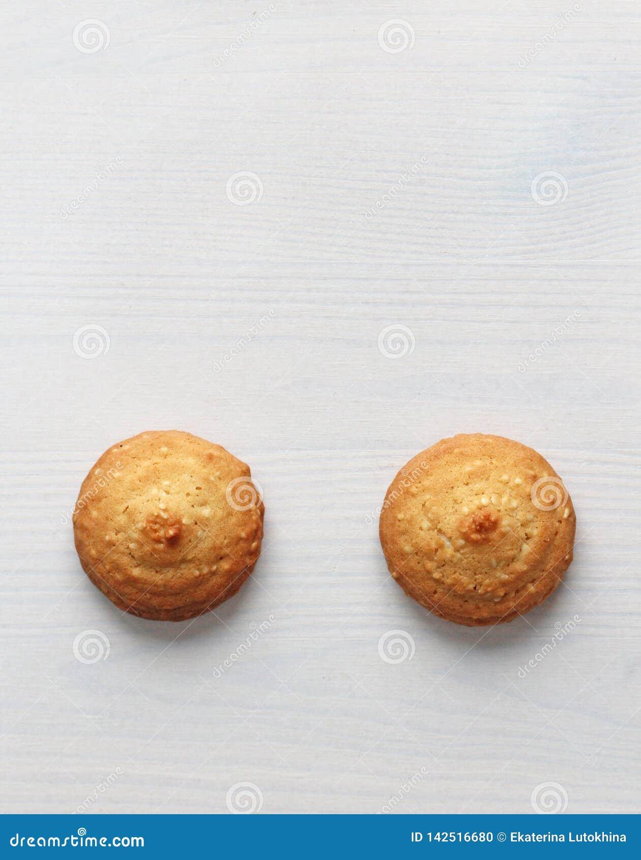 Biscotti su un fondo bianco, simile ai capezzoli femminili Capezzoli sexy sotto forma di biscotti Umore, doppio significato